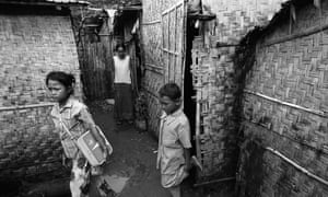 Channa, 12, sets out with her bathroom scales, watched by her brother Pov, nine, and mother Rihorn