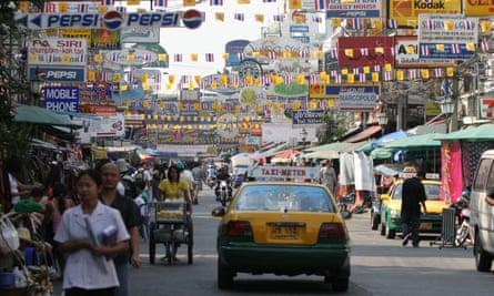 A taxi drives down busy Khao San Road, Bangkok, Thailand.