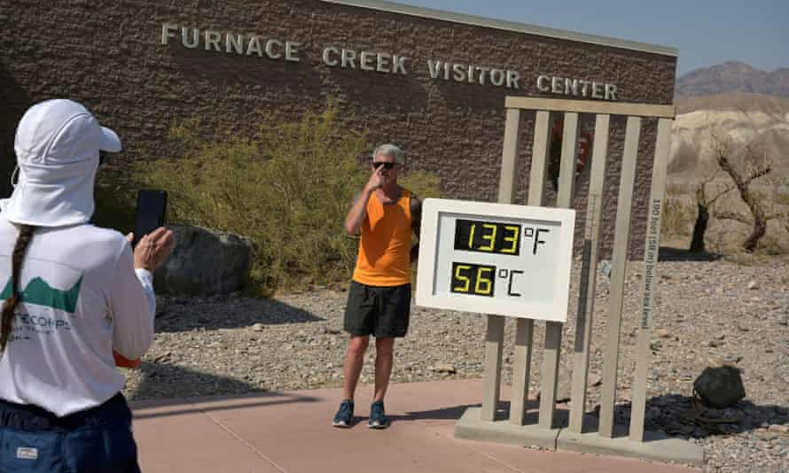 A person poses for a photo next to a thermometer readout in Death Valley, California