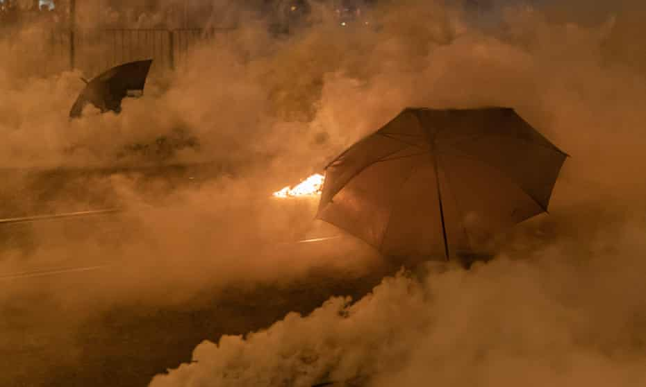 Umbrellas in a cloud of tear gas outside Tai Koo MTR station in Hong Kong, 2019.