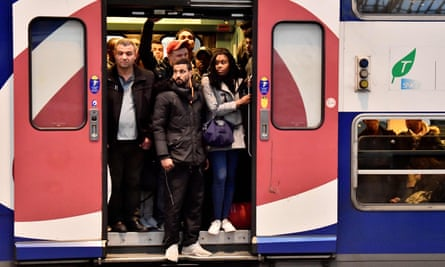 Commuters stand in the doorway of a crowded train in Paris.
