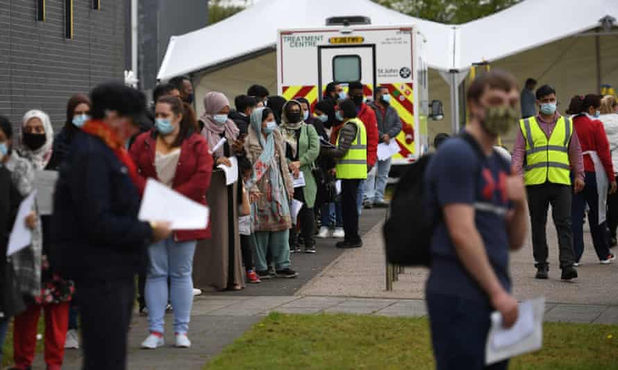 People queue at a temporary Covid-19 vaccination centre in Bolton, north-west England.