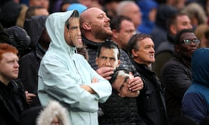 Some West Ham fans taunt the visiting fans with Carlos Tevez masks.