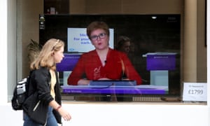 A woman walks past a TV screen in Edinburgh as Nicola Sturgeon takes part in a virtual sitting of the Scottish parliament.