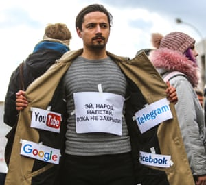 A protester for internet freedom displays different internet media companies logos inside his trenchcoat.