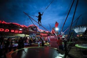 A child bounces on a trampoline at a fair in Titu