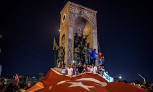 People wave a giant Turkish national flag at Taksim Square.