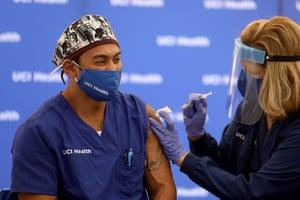 Erik Mara, a respiratory therapist at UCI Health, receives a Pfizer coronavirus vaccine at the University of California, Irvine Medical Center.