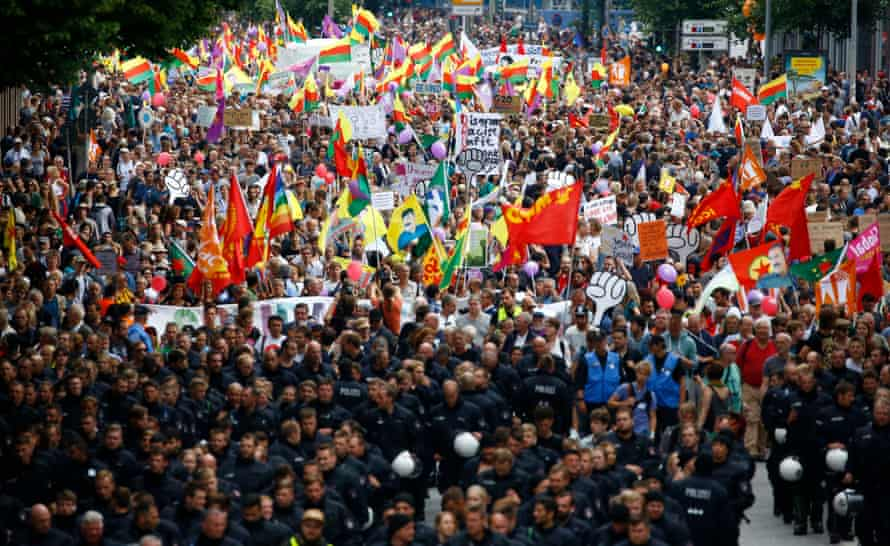 Police walk ahead of protesters demonstrating against the G20 summit in Hamburg