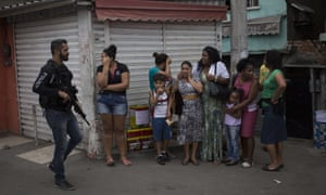 A police officer walks past distressed residents in the Alemão favela.