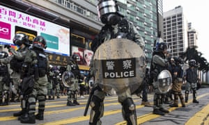 Security forces stand guard as protesters take part in an anti-government protest in Tsim Sha Tsui, Hong Kong