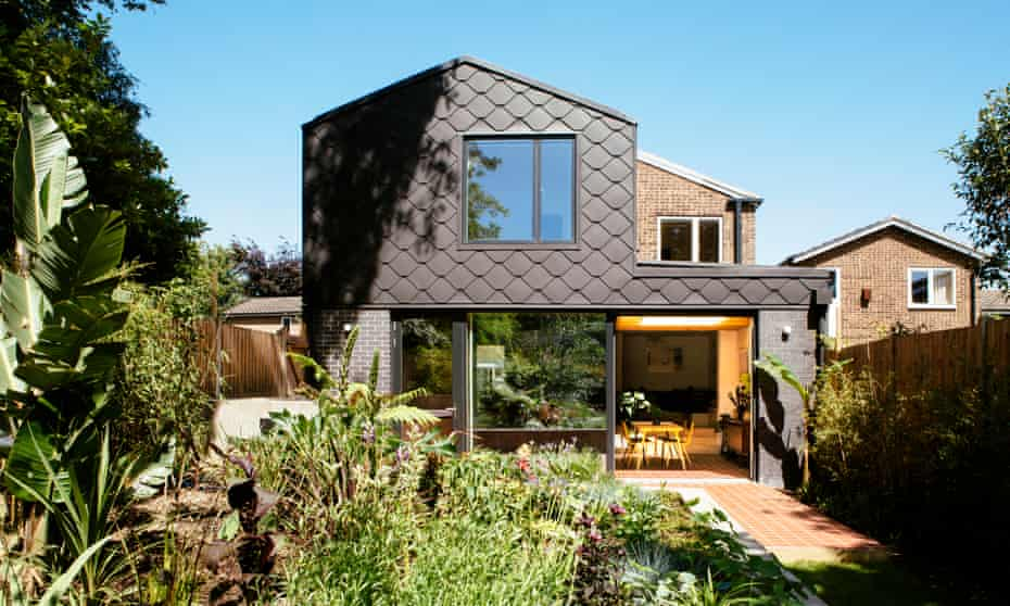 A zinc-tiled extension mirrors the form of the original 1960s house and overlooks a concrete planter.