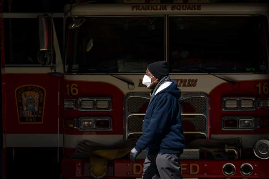 A man wearing a face mask walks past the Franklin Square fire station on April 7, 2020 in Washington, DC. More than 430 employees from the District of Columbia Fire Department and Metropolitan Police Department were quarantining due to potential coronavirus exposure. As of Monday, 34 members of the fire department, including an assistant fire chief, have tested positive for COVID-19.