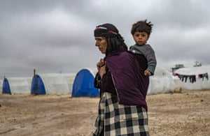 An elderly displaced Syrian woman carries a child in the Washukanni camp for the internally displaced near the city of Hasakeh.