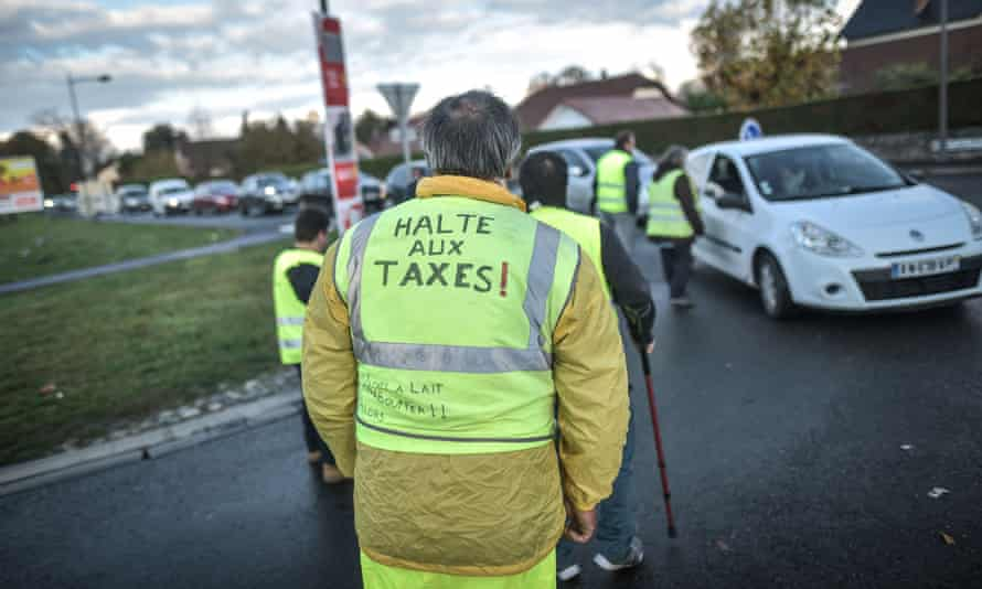Man in yellow waistcoat reading 'stop the taxes' in French