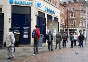 People queue to use banking facilities within a Barclays branch in Nottingham city centre during England's third national lockdown to curb the spread of coronavirus.