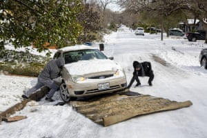 Ivan Gonzales, left, works with his brother-in-law Gabriel Martinez to assist a motorist using a carpet up a hill along the snow-covered Cherrywood Road in Austin, Texas, on Tuesday, Feb. 16, 2021.