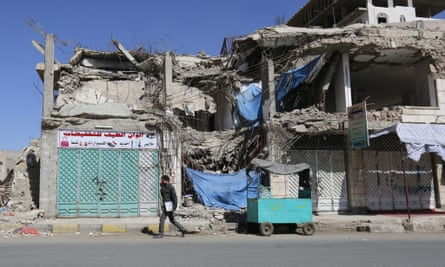 A Yemeni student walks past a building destroyed by an airstrike in Sana'a.