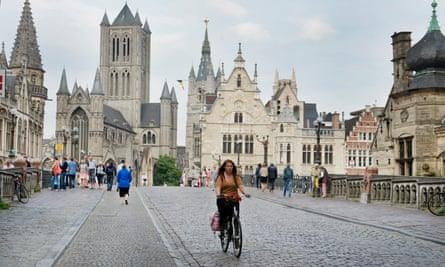 A cyclist rides through the city centre in Ghent, where three-quarters of residents are in favour of plans to expand the pedestrian zone.