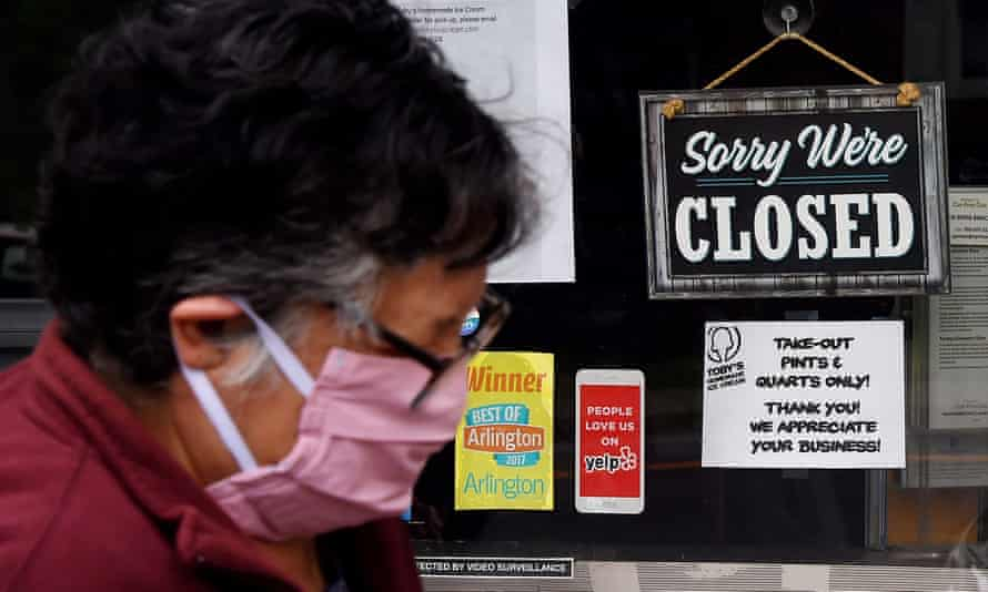 A woman wearing a face mask walks past a sign in the window of a closed food store