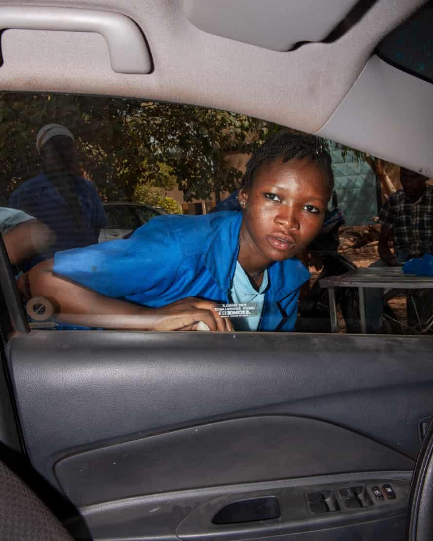 A girl works on a car