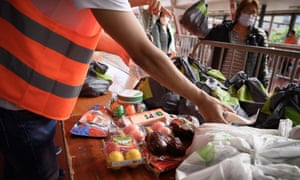 Volunteers hands out food bags at a free distribution point for the people in need in Geneva.