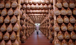 A worker walking in a special room where Parma ham is hung to dry in Langhirano, Italy.