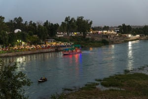 Boats cruise along the Tigris at sunset in Mosul.