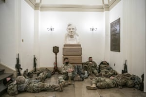 Members of the National Guard rest in a hallway of the Capitol building underneath a bust of former president Abraham Lincoln.