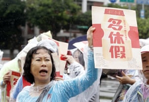 Taipei, Taiwan. A worker holds a placard that reads 'More Days Off' during a Labour Day rally