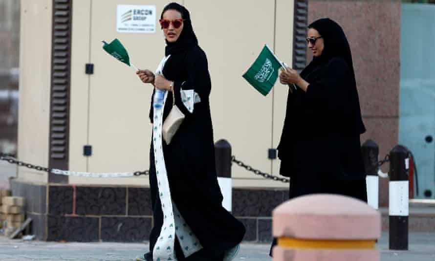 Saudi women hold national flags during Saudi National Day in Riyadh, Saudi Arabia Friday.