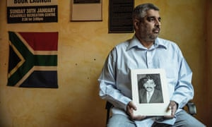 Imtiaz Cajee, nephew of Ahmed Timol, holds a portrait of his uncle