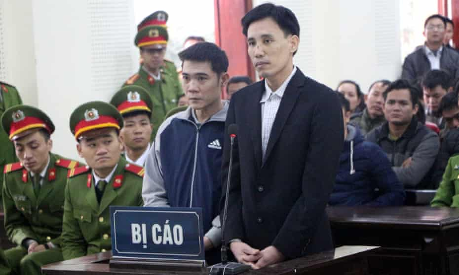 Vietnamese activist Hoang Duc Binh (centre L) standing inside the courtroom with co-accused Nguyen Nam Phong in Nghe An