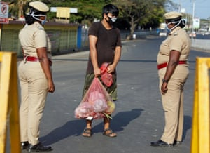 A man carrying vegetables is stopped by police at a barricade in Chennai