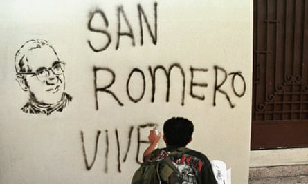 """A Catholic faithful paints a sign reading, """"San Romero Lives"""" on 24 March 1999, during a mass to commemorate the 19th anniversary of the killing of Oscar Romero."""