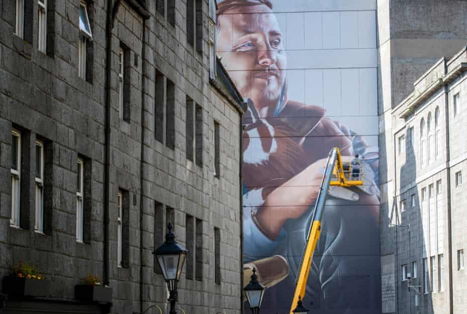 Street artist Sam Bates, AKA Smug, creates a mural during the Nuart festival.