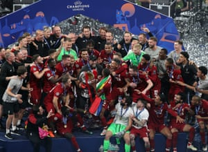 Liverpool players and manager Jurgen Klopp celebrate with the trophy.