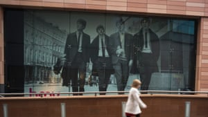 A woman walks past a giant photograph of the Beatles in Liverpool