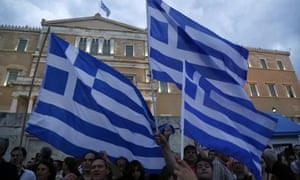 Demonstrators hold Greek flags during a rally organised by supporters of the yes vote for the upcoming referendum