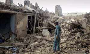 An Afghan police officer investigates the destruction in the eastern Wardak province of Afghanistan.