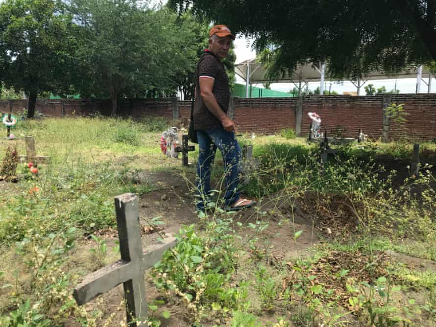 A gravedigger tours unmarked graves in the public cemetery in Tecomán, Mexico's most murderous municipality