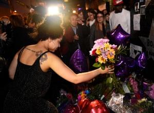 A fan leaves flowers outside First Avenue, the nightclub featured in the movie Purple Rain, in Minneapolis.