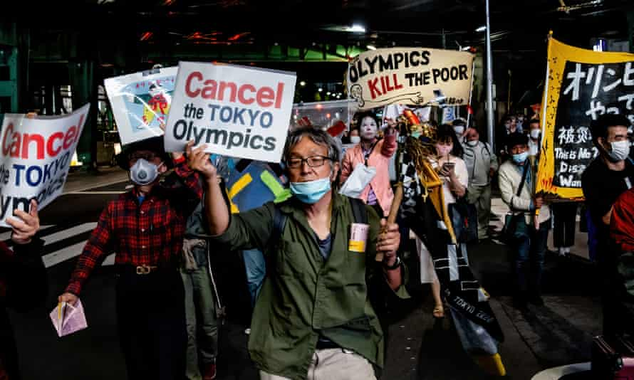 Demonstrators protest against the Tokyo Olympics with billboards and banners shouting 'Just stop it' marching through the Shimbashi and Ginza area on 17 May.