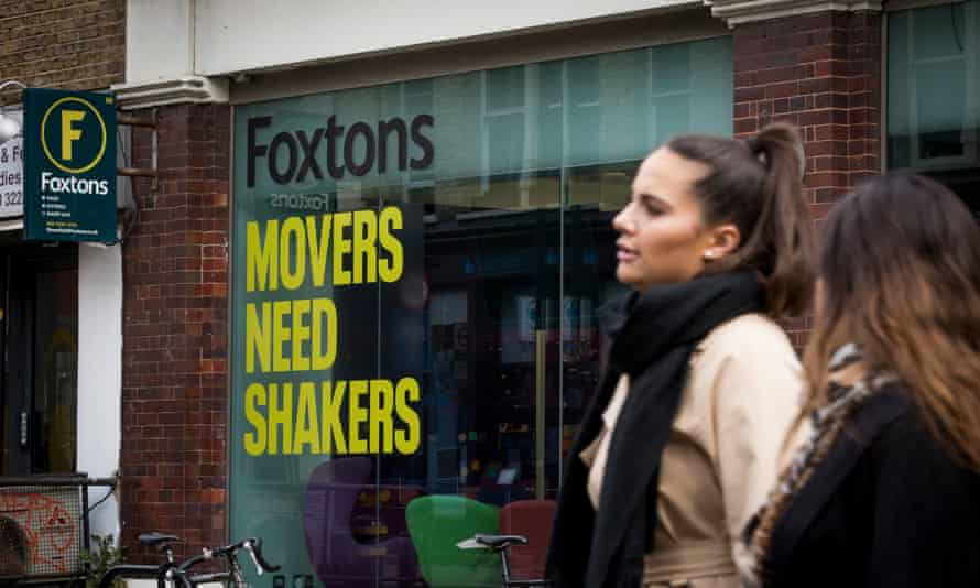 """A branch of Foxtons with two women standing outside it; on the window is the slogan """"Foxtons: Movers Need Shakers' in black and  yellow"""