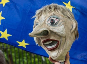 A puppet of Theresa May in front of an EU flag.