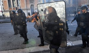 Riot police officers walk near burning garbage in Marseille, on the sideline of a demonstration of high school students.