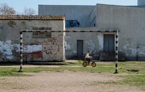 A boy rides a bicycle near a goalpost in Yevpatoria, Crimea