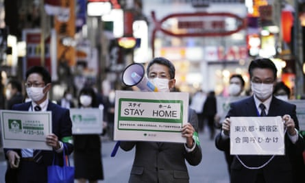 Staff of the Tokyo's city authority urge people to go home from the Kabukicho district in April.