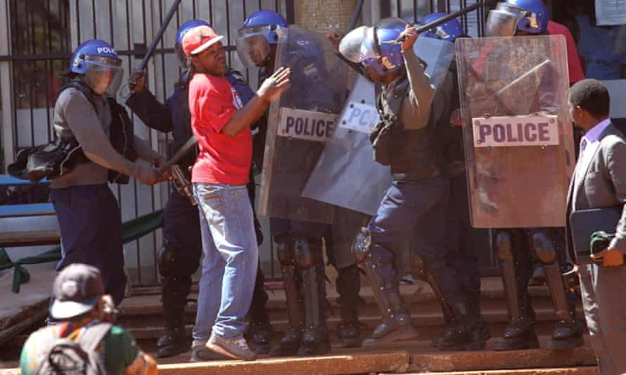 Zimbabwean riot police confront a protester during a demonstration in Harare