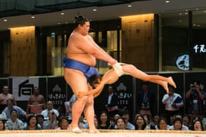Sumo wrestler plays with child